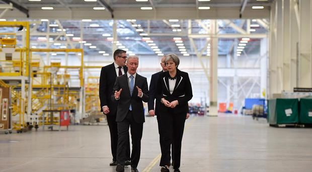 British Prime Minister Theresa May is shown around by Michael Ryan (L), president of Bombardier Aerostructures and Engineering services division, during a visit to the Belfast Bombardier factory on February 12, 2018 in Belfast, Northern Ireland. (Photo by Charles McQuillan/Getty Images)