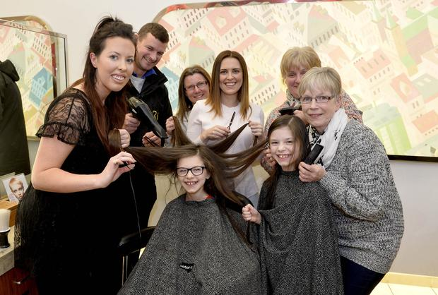 Stylist Jess Lynn prepares Grace for getting her long hair cut with mum Carolynn, dad Robbie, twin sister Abbie, aunt and grannies all lending a helping hand