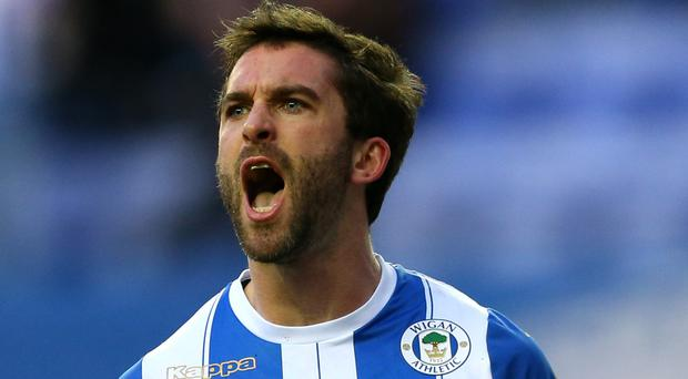 Net gains: Will Grigg celebrates his classy winner against Manchester City