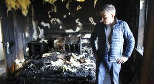 House owner Matthew Davey surveys the extensive fire damage caused by the intruders to his home in Clough, Co Down