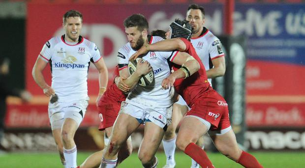 Got Stu: Ulster try scorer Stuart McCloskey is tackled by Scarlets' Ryan Elias