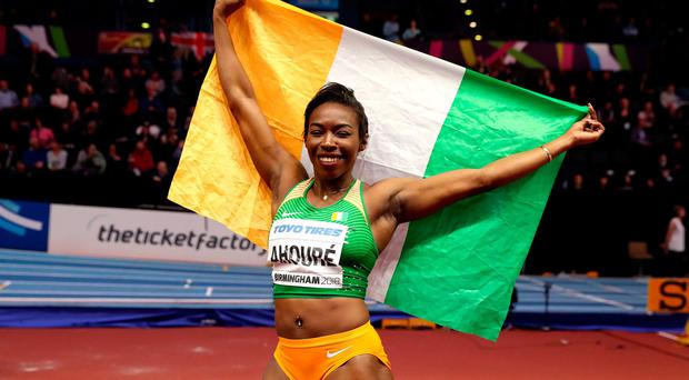 Ivory Coast's Murielle Ahoure celebrates winning gold in the Women's 60m final - with an Irish fan's flag.