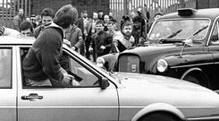 One of the Army Corporals draws his weapon after being surrounded by a crowd at the funeral of IRA man Kevin Brady, who was killed in the Milltown attack