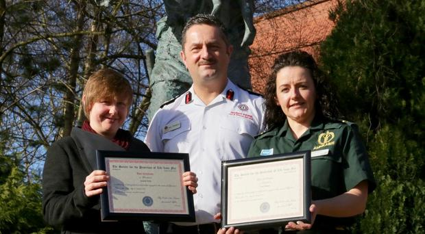 Chief Fire & Rescue Officer Gary Thompson presented Certificates of Bravery on behalf of the Society for the Protection of Life from Fire to Amanda White (L) and Paramedic Tara Wallace (R) for their rescue of a woman from a house fire in Annahilt.