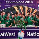 The Ireland team celebrate with the Triple Crown and Six Nations trophies as they pose for their Six Nations Grand Slam victory after the Six Nations international rugby union match between England and Ireland at the Twickenham, west London, on March 17, 2018. / AFP PHOTO / Ben STANSALLBEN STANSALL/AFP/Getty Images