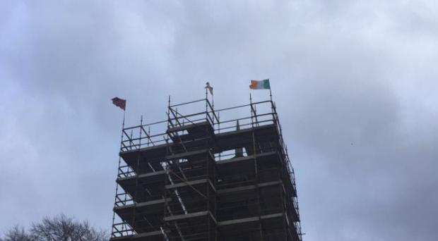 Sinn Fein members have removed tricolour flags placed on a Church of Ireland building