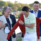Perfect fit: Arnold Palmer's grandson, Sam Saunders and widow Kit Palmer help Rory put on the championship sweater