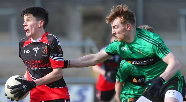 Getting the arm in: James Kelly is hounded by Tiernan Mackle