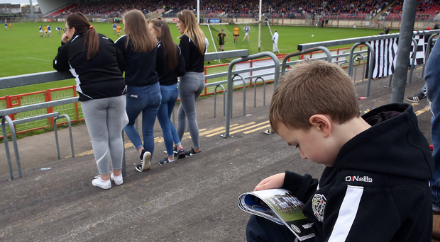 Changes aplenty: a fan reads a match programme, but the printed line-up is sure to have changed