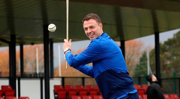 Taking aim: Jonny Evans tries his hand at hurling yesterday during the launch of Sport Uniting Communities, a collaboration between the IFA, Ulster GAA and Ulster Rugby