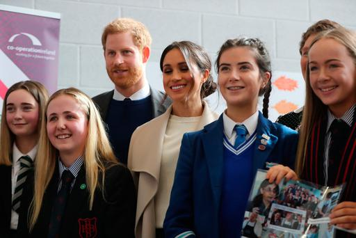 Prince Harry and Meghan Markle stand with school children during a visit to the Eikon Exhibition Centre in Lisburn. Photo: Niall Carson/PA Wire