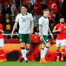 Tough night: Declan Rice and James McClean show their disappointment after Turkey's winner
