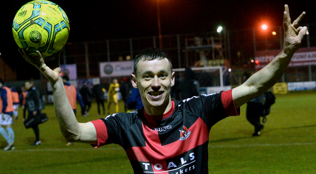 Terrific treble: Paul Heatley celebrates with the match ball after hitting a hat-trick to sink Warrenpoint