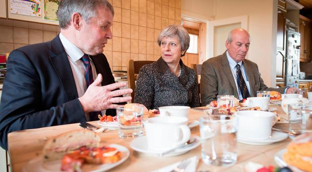 Prime Minister Theresa May having lunch with farmers at Fairview Farm in Bangor, Northern Ireland during a tour of the four nations of the UK, with a promise to keep the country united one year before Brexit. Stefan Rousseau/PA Wire