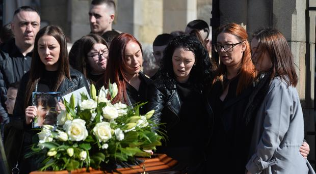 Mourners comfort each other as the funeral of Ann McKernan