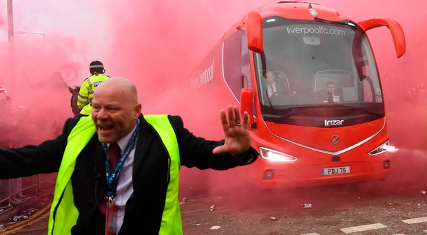 Red mist: Liverpool supporters welcome their team's coach