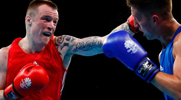 Fighting chance: Steven Donnelly (red) on his way to victory against Wales' Kyran Jones at the Commonwealth Games in Australia yesterdayWales
