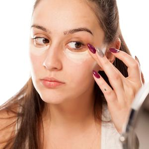 A young woman applies a concealer under the eyes