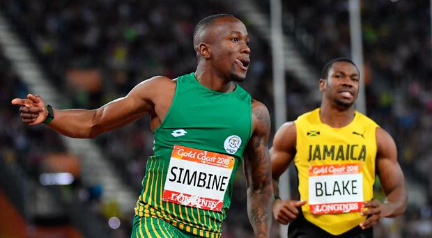 Lagging behind: Yohan Blake looks on as Akani Simbine claims gold in the 100m at the Commonwealth Games