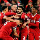 Super Mo: two-goal hero Mo Salah is mobbed after putting Liverpool on the way to a 5-2 first leg victory over Roma at Anfield last night