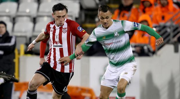 Tough to take: Derry's Aaron McEneff (left) battles with Graham Burke of Rovers during City's record defeat last month