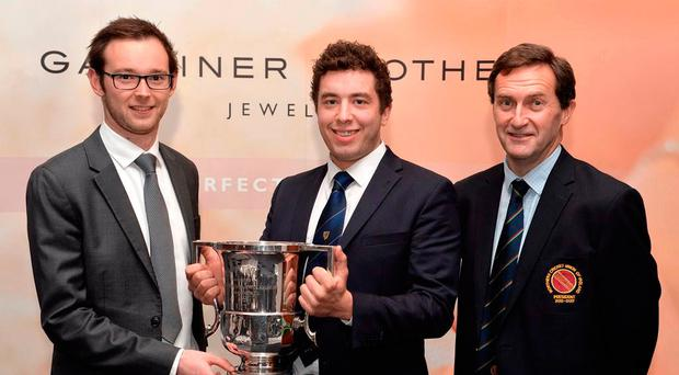 Silver service: Armagh captain Matthew Steenson receives last year's Section One trophy from Michael Warke of Gardiner Bros, with NCU president Peter McMorran looking on