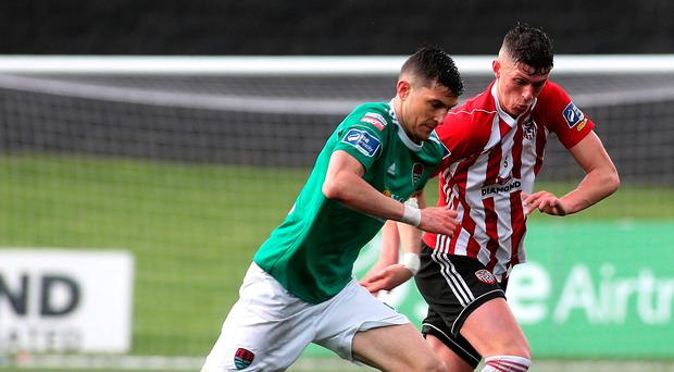 Tight race: Derry's Eoin Toal attempts to muscle in on Cork's Graham Cummins at the Brandywell