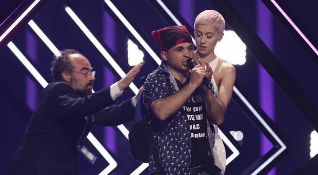 A stage invader grabs the microphone from SuRie (Armando Franca/AP)