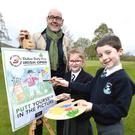 Brian McIlroy of the Rory Foundation and primary school pupils Tiarna (6) and Sean (7), brush up on their drawing skills to launch the Putt Yourself In The Picture competition.