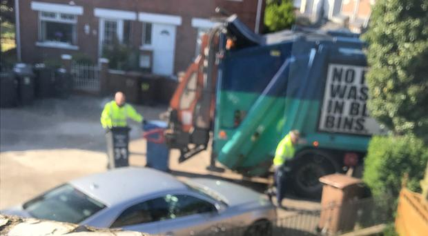 Binmen appear to be putting a blue bin containing recyclable material in with rubbish going to landfill.