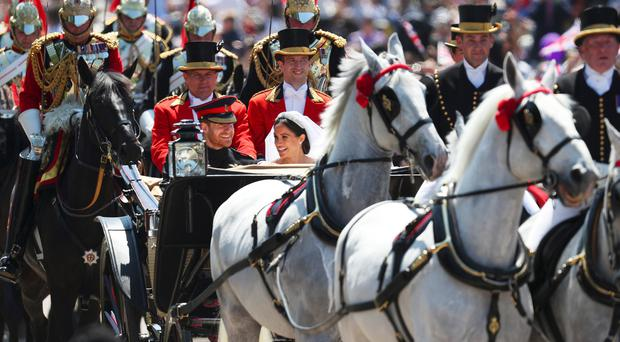 Prince Harry, Duke of Sussex and the Duchess of Sussex ride a horse-drawn carriage, after their wedding ceremony at St George's Chapel in Windsor on May 19, 2018 in Windsor, England. (Photo by Hannah McKay- WPA Pool/Getty Images)