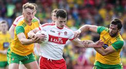 Tough day: Derry's Kevin Johnston with Donegal's Stephen McMenamin and Odhran McNiallais
