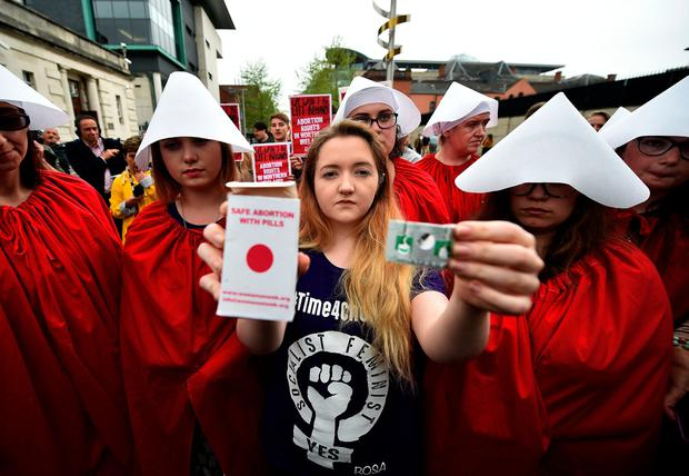Eleanor Crossey Malone displays an abortion pill packet after taking a pill as abortion rights campaign group ROSA, Reproductive Rights Against Oppression, Sexism and Austerity distribute abortion pills from a touring bus on May 31, 2018 in Belfast. (Photo by Charles McQuillan/Getty Images)