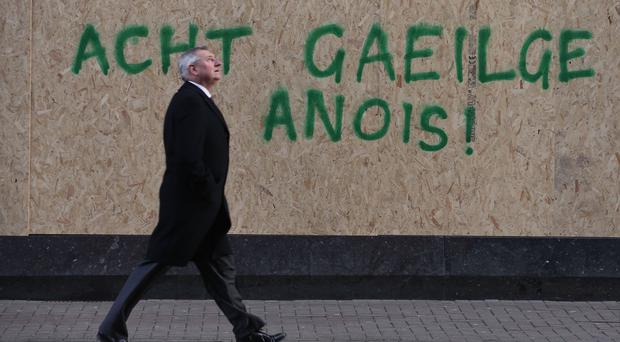 A man walks past graffiti calling for an Irish Language act (Niall Carson/PA)