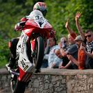 Tribute: Dan Kneen's brother, Ryan is cheered by fans as he wheelies over Sulby Bridge during a tribute lap to his brother who lost his life in a crash on Wednesday evening