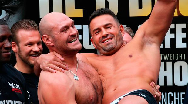 Light weight: Tyson Fury lifts opponent Sefer Seferi during the weigh-in yesterday