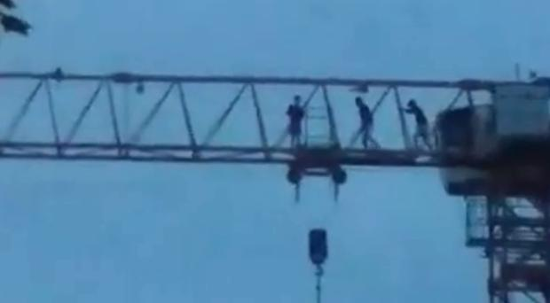 Three people were filmed scaling a huge crane in Londonderry, Northern Ireland on Saturday, June 9.