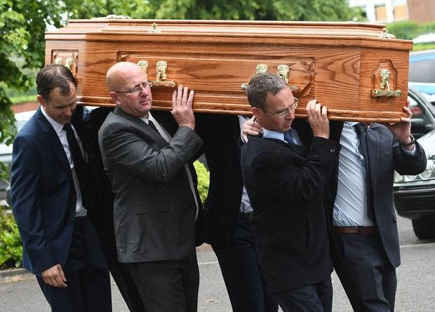 Hugh Jnr (left) carries his fathers coffin with family and friends during the funeral of Hugh Dougal. Pic Colm Lenaghan/Pacemaker
