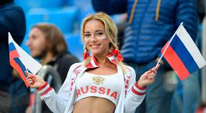 A Russia fan waves flags prior to the Russia 2018 World Cup Group A football match between Russia and Egypt at the Saint Petersburg Stadium in Saint Petersburg on June 19, 2018.