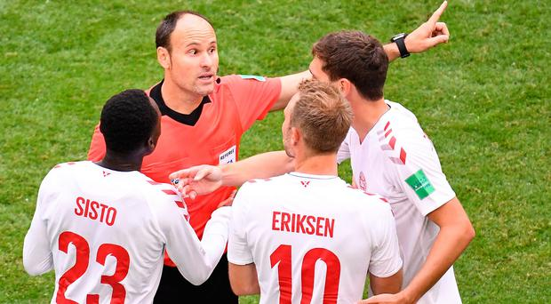 Danish players surround the referee after Australia were awarded a controversial penalty by VAR