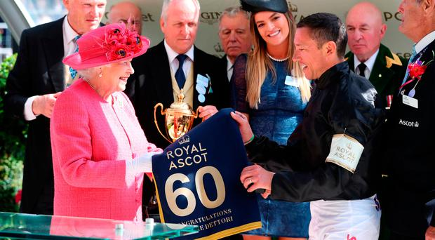 High honour: Queen Elizabeth II congratulates Italian jockey Frankie Dettori after he won the Gold Cup in a thrilling finish while aboard Stradivarius yesterday at Royal Ascot