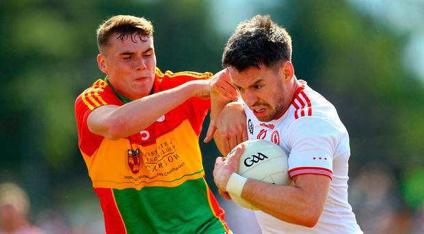 Close quarters: Tyrone's Matthew Donnelly holds off Jordan Morrissey