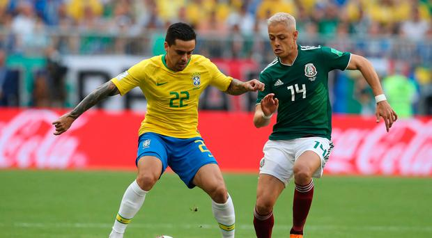 Cool head: Brazil's Fagner attempts to hold off Mexico ace Javier Hernandez