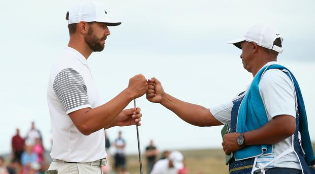 Erik van Rooyen of South Africa bumps fists with his caddie during another impressive day at the Irish Open.