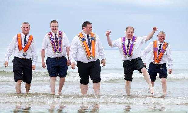Gareth Lough, Jonathan Bready, Joseph Magill, Robert Bready and Willaim Lough bathe their feet on the beach during a break in the parade. Picture by Jonathan Porter/PressEye