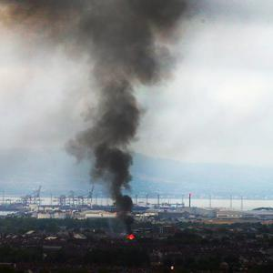 Bloomfield Walk bonfire in east Belfast, which was set on fire during the night, as seen from the Castlereigh Hills. A High Court order late on Tuesday night stated that the bonfire should be reduced in size as it was a danger to surrounding homes. Picture by Jonathan Porter/PressEye
