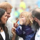 The Duke and Duchess of Sussex meet three year old Walter Kieran as they watch traditional Gaelic sports being played at Croke Park on the second day of their visit to Dublin, Ireland (Chris Jackson/PA)
