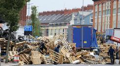 General view of the PSNI officers at the scene of the Cluan Place bonfire in east Belfast as contractors remove material from the 11th night bonfire. Photo by Kelvin Boyes / Press Eye.