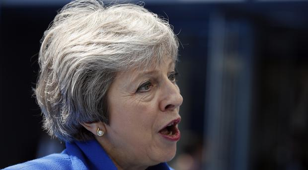 Prime Minister Theresa May speaks as she arrives for a summit of heads of state and government at Nato headquarters in Brussels (Francois Mori?AP)