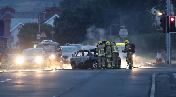 Firefighters deal with a burnt out car in the Cherryhill area of Dundonald (Niall Carson/PA)